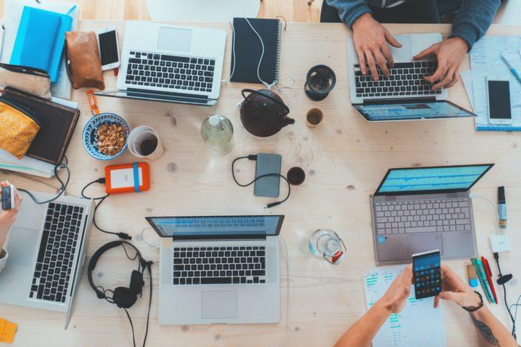 テーブルでパソコン作業する複数のIT留学生