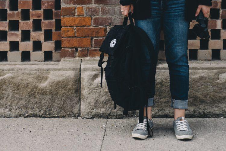 勉強用のバッグを持って立つ生徒